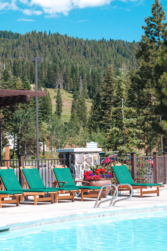 Idaho Resorts: Tamarack Resort.  A view of the pool at Tamarack Resort's hotel accommodations overlooking the former golf course.  The ski hill and mountain biking trails are visible in the distance, past green cushioned deck chairs lining the swimming pool.