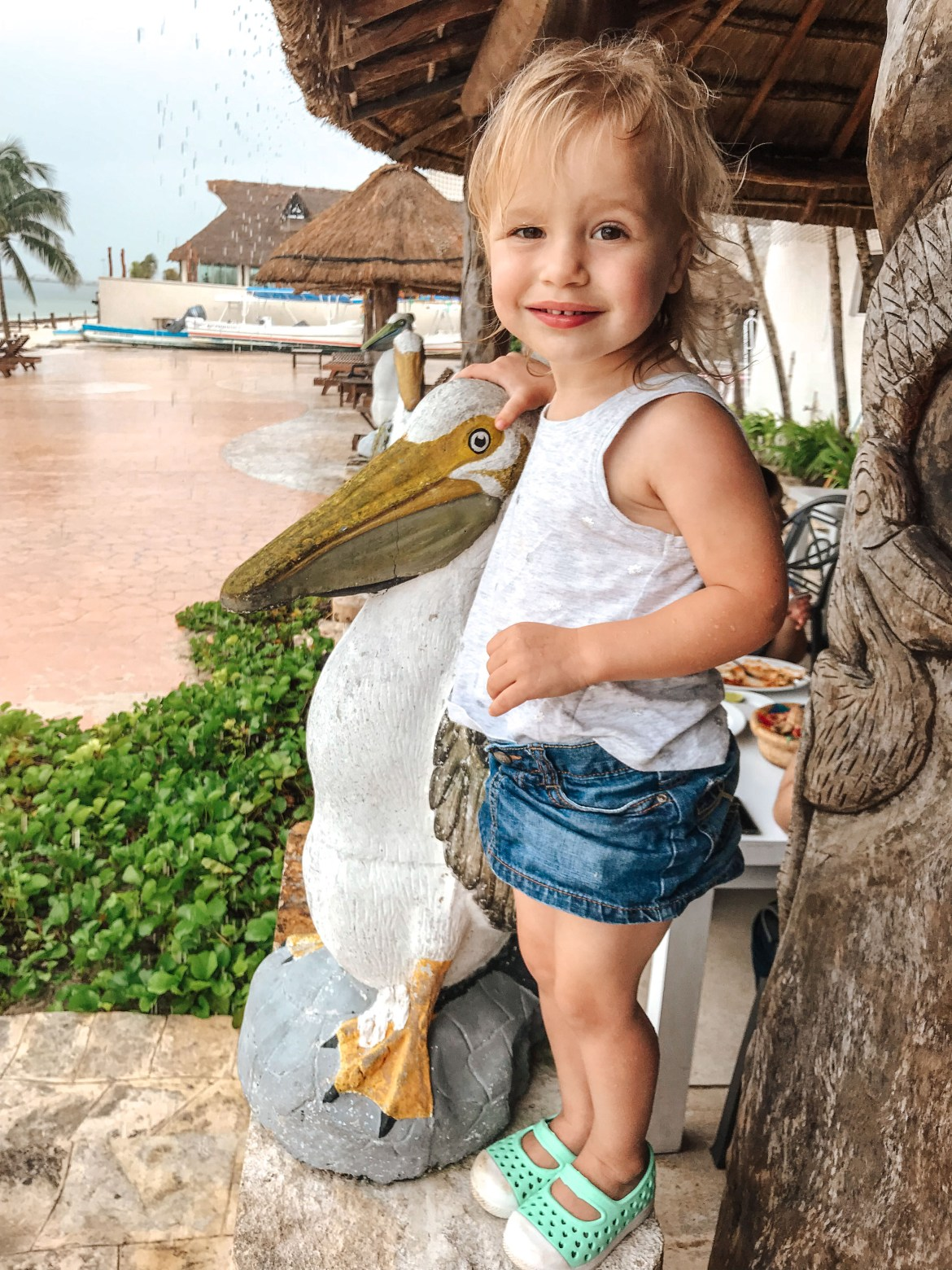 Things to do in Puerto Morelos Mexico. A young girl stands next to a statue of a pelican under a thatched roof as rain pours onto an outdoor cement patio in Mexico's Puerto Morelos, a town South of Cancún along the Riviera Maya.