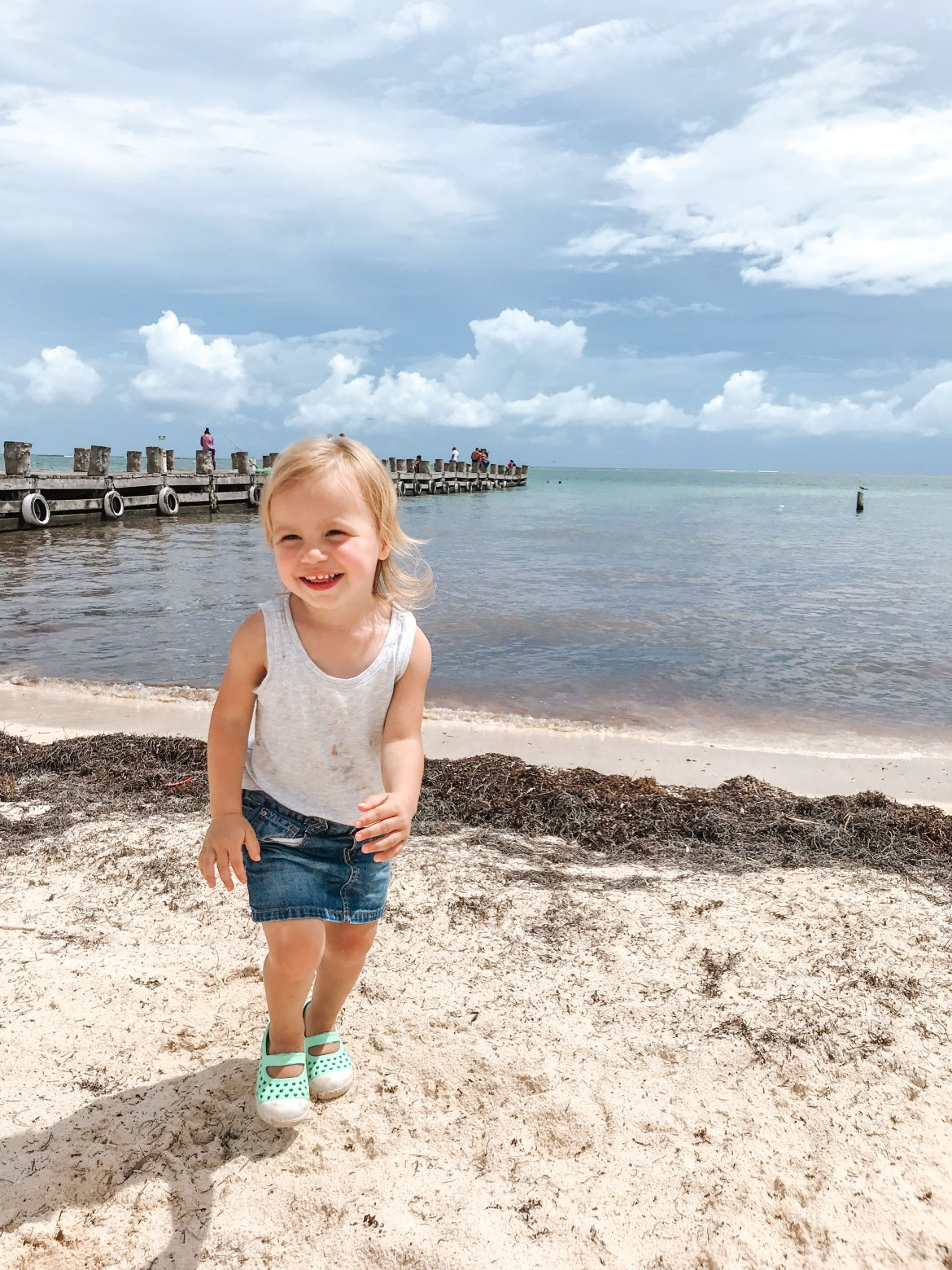 Things to do in Puerto Morelos Mexico. A young girl stands on a white sand beach at Mexico's Puerto Morelos, South of Cancún along the Riviera Maya.  The sun shines over the turquoise-blue waters of the Caribbean Sea and a pier juts out into the water.