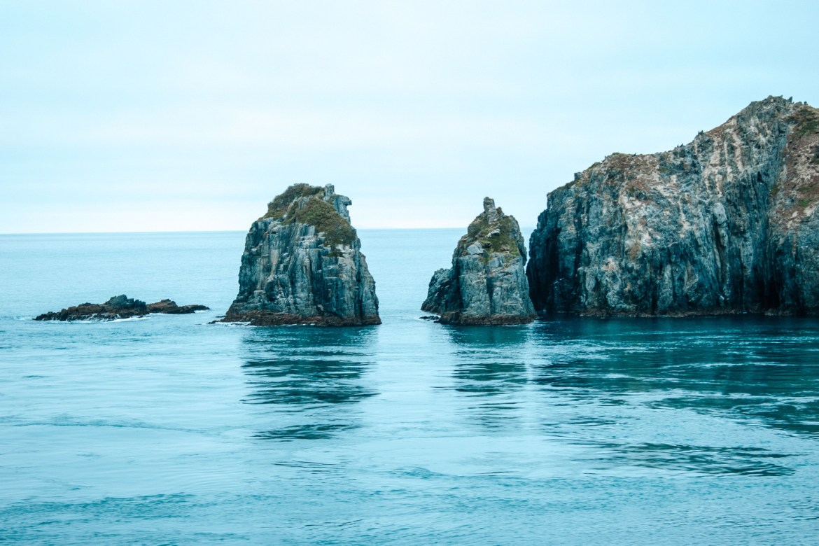 Coastal Landscapes.  Numerous rock outcroppings jut out from Cook Strait, leading away from the South Island.  The perspective looks out from atop New Zealand's Interislander ferry connecting the South Island and North Island from Picton to Wellington through Cook Strait.