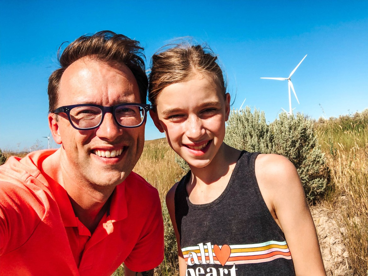 Day 1 of our recommended Yellowstone Vacation Itinerary: Yellowstone Road Trip.  A father and daughter stand on a rural dirt road near Massacre Rocks State Park and American Falls, Idaho.  A large wind turbine is visible against bright blue sky behind them.  Brown foliage surrounds Deeg Road in Eastern Idaho's high desert.