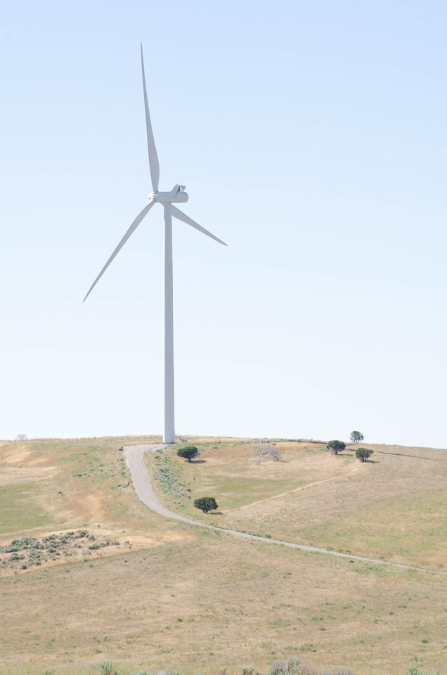 Free pics: A giant wind turbine sits in rural farmland near Massacre Rocks State Park and American Falls, Idaho.  Washed-out skies contrast with the long, white arms of the turbines as they spin in the wind in Eastern Idaho.