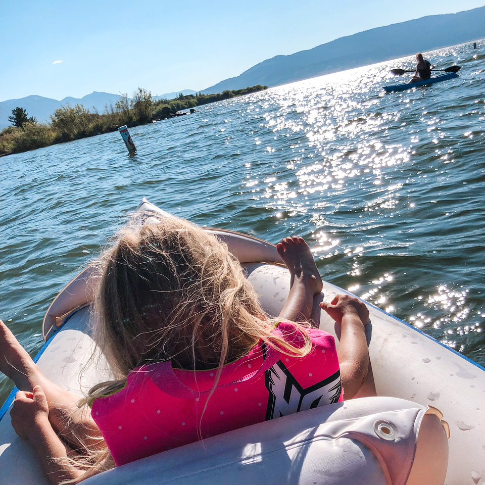 A young girl sits in the front of a two-person, inflatable kayak at Idaho's Henrys Lake State Park.  The park, just 15 miles from the West Gate to Yellowstone National Park, is known for native cutthroat trout, world-class fishing, and gale-force winds.