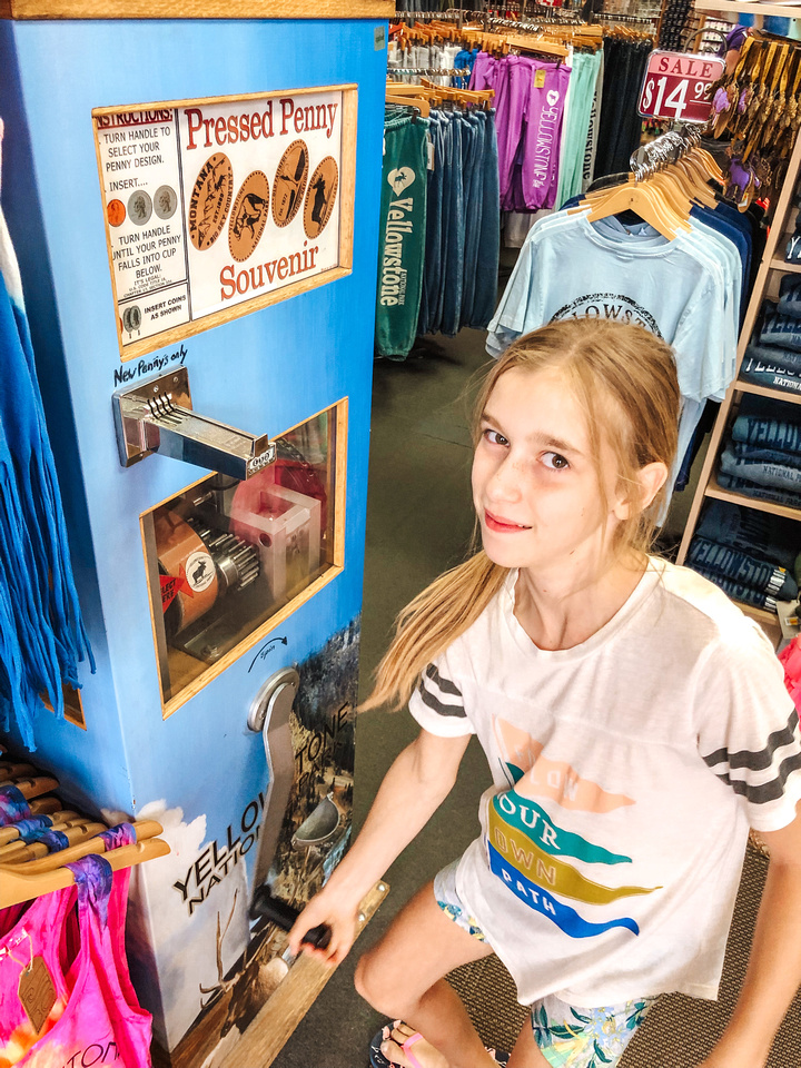 A young girl stands in front of a souvenir penny pressing machine that creates pressed pennies from Yellowstone with a variety of imprints, including buffalo, geysers, and other iconic landscapes.  T-shirts on racks for sale fill the background behind the machine.