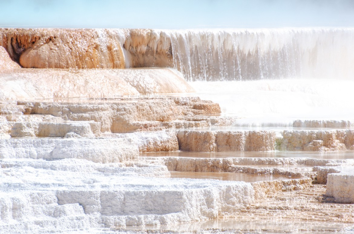 Yellowstone Hot Springs: The upper-most section of Mammoth Hot Springs.  White and orange platforms hold hot water as it spills down the hillside at one of Yellowstone's most famous sites.