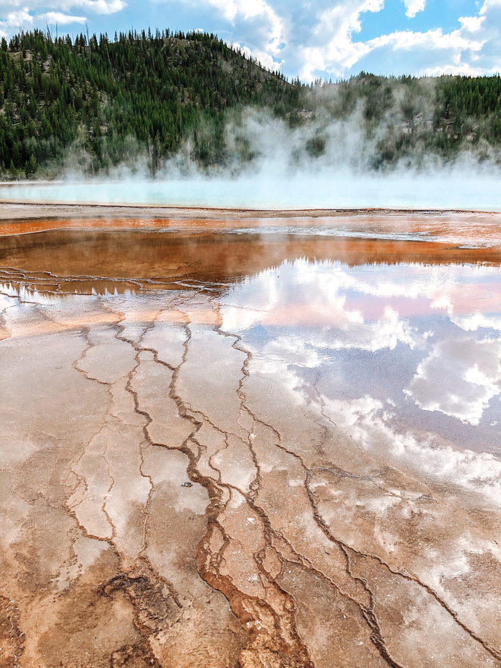 A view atop Grand Prismatic Spring in Yellowstone National Park, Wyoming.  From the air, Grand Prismatic is one of the most colorful and eye-catching thermal springs in Yellowstone.  Viewing platforms and a raised walkway carry visitors across and through the massive springs.
