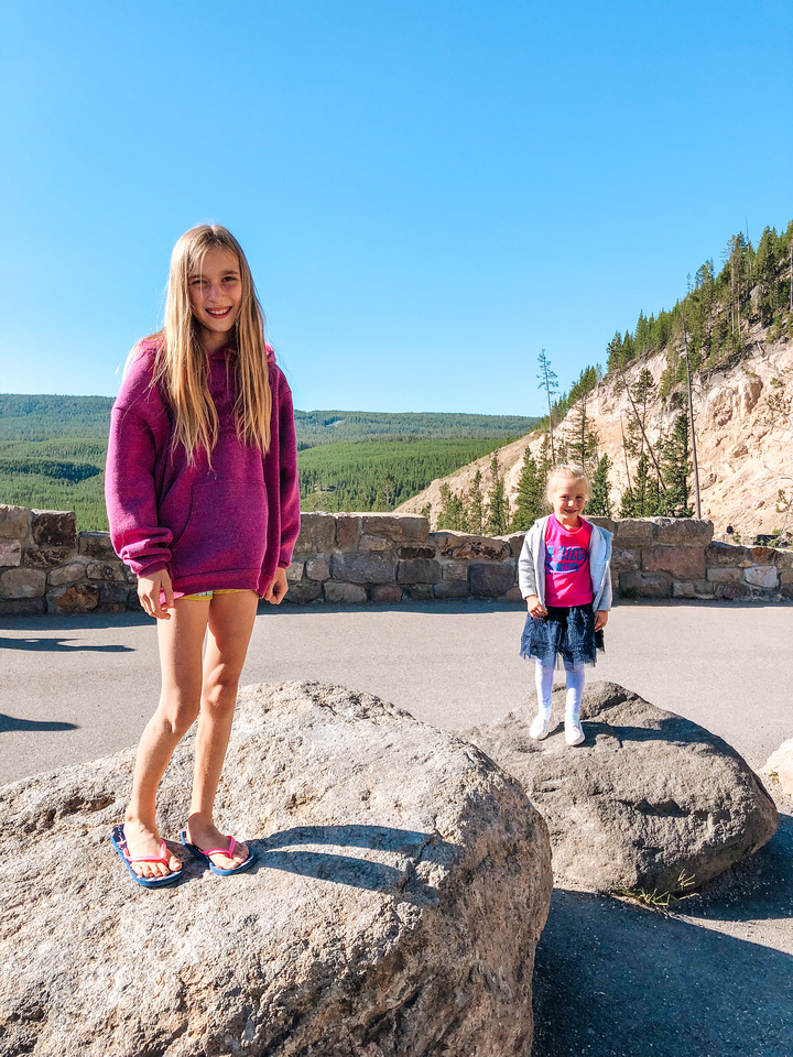 A view of the Gibbon Falls Overlook in Yellowstone National Park, Wyoming.  Two young girls stand on large boulders at the overlook to the falls.