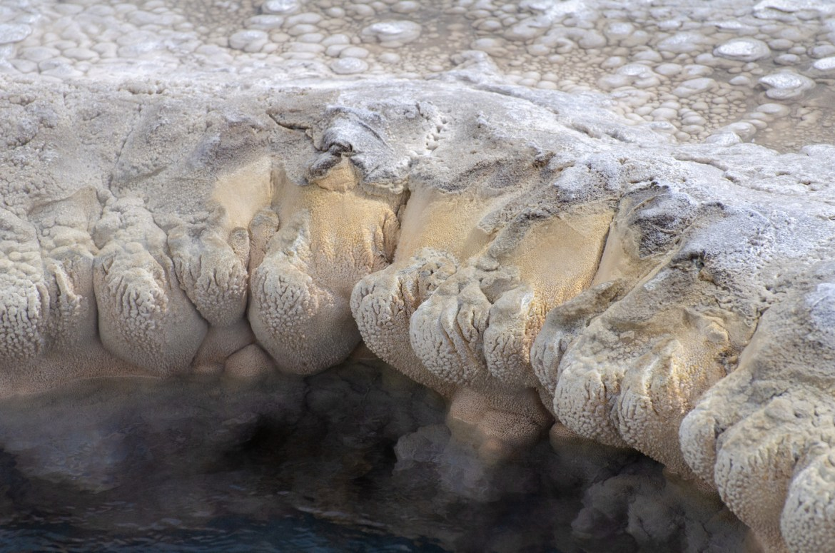 Yellowstone Vacation: Another view of thermal hot springs at the Upper Geyser Basin in Yellowstone National Park, Wyoming. In this photo, round, calcified material bulges over and down toward hot springs pools below.