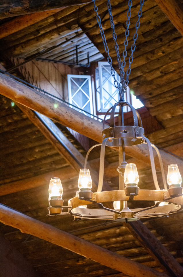 An interior view of the Old Faithful Inn in Yellowstone National Park, Wyoming.  This photo, taken in the main dining room, shows an antique lantern chandelier and an open window through the wooden roof and support beams.