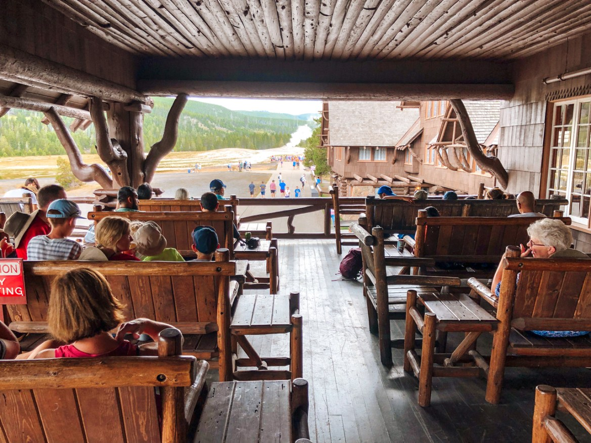 Yellowstone's Old Faithful Inn. An exterior view of Yellowstone National Park's Old Faithful Inn, the iconic Lodge near the Old Faithful Geyser. Visitors sit in the partially-covered viewing platform atop the Inn, looking out to Old Faithful.