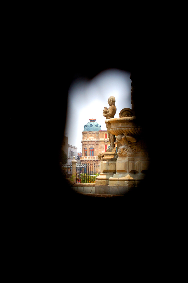 This image shows a copper cupola on a colonial building in Mexico City, seen through a keyhole. The domed building is an example of Greek Revival and neoclassical architecture.