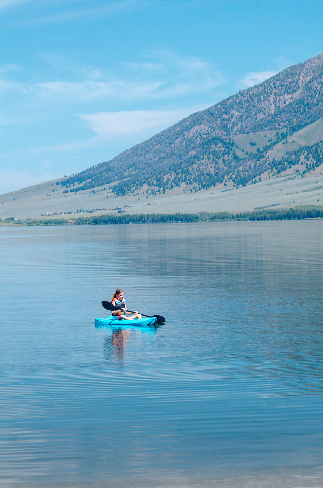 A view of Henrys Lake from a kayak. The Targhee National Forest and mountain range are visible in the distance.
