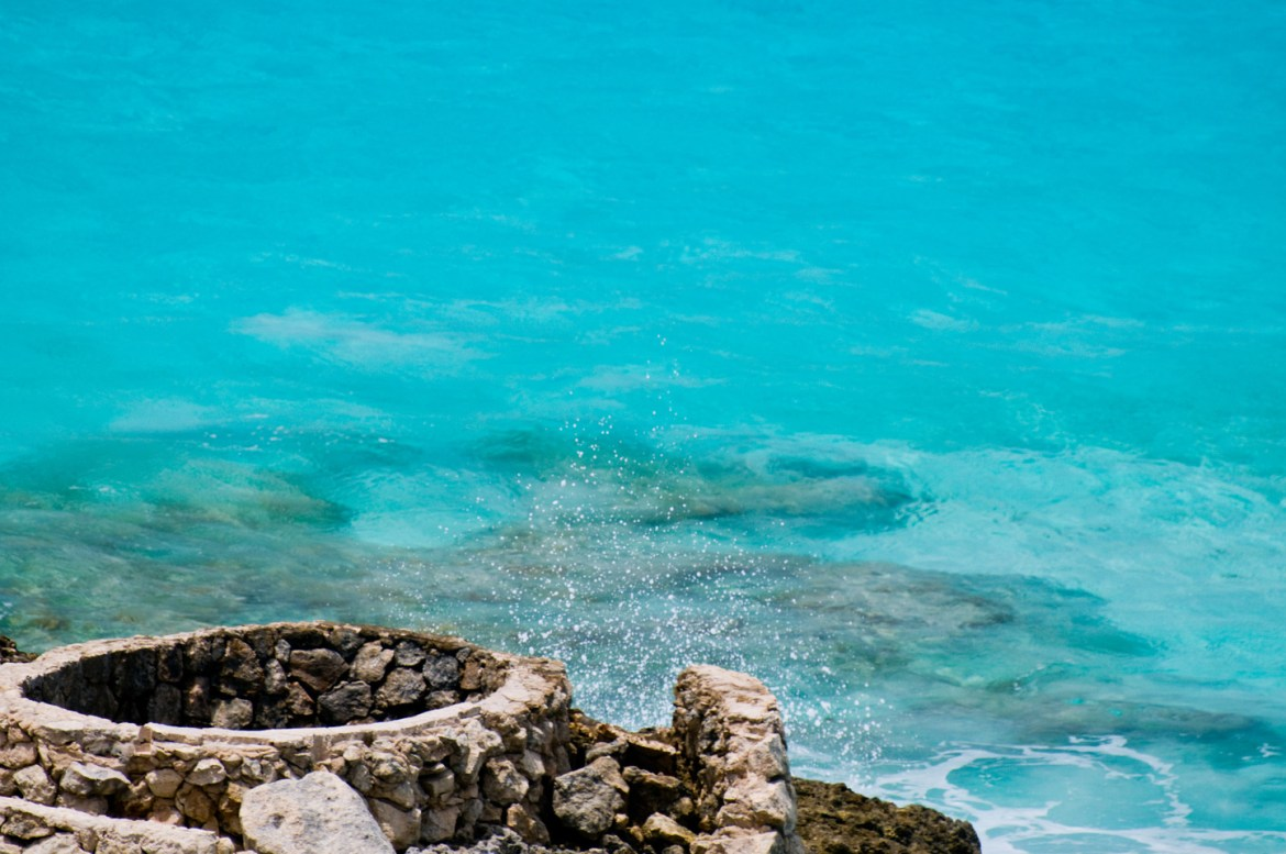 Turquoise water and a stone structure between Cancun, Mexico and Isla Mujeres.