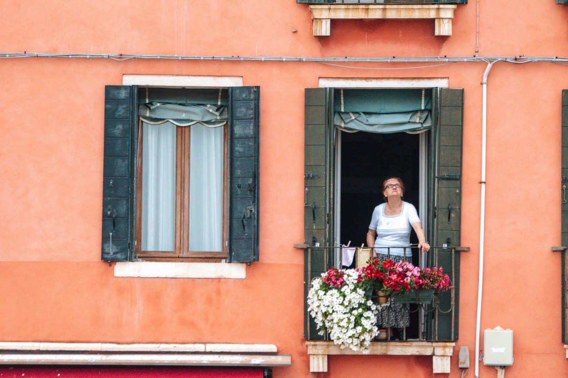 A woman looks up and out her second-story window above a busy Venetian street.