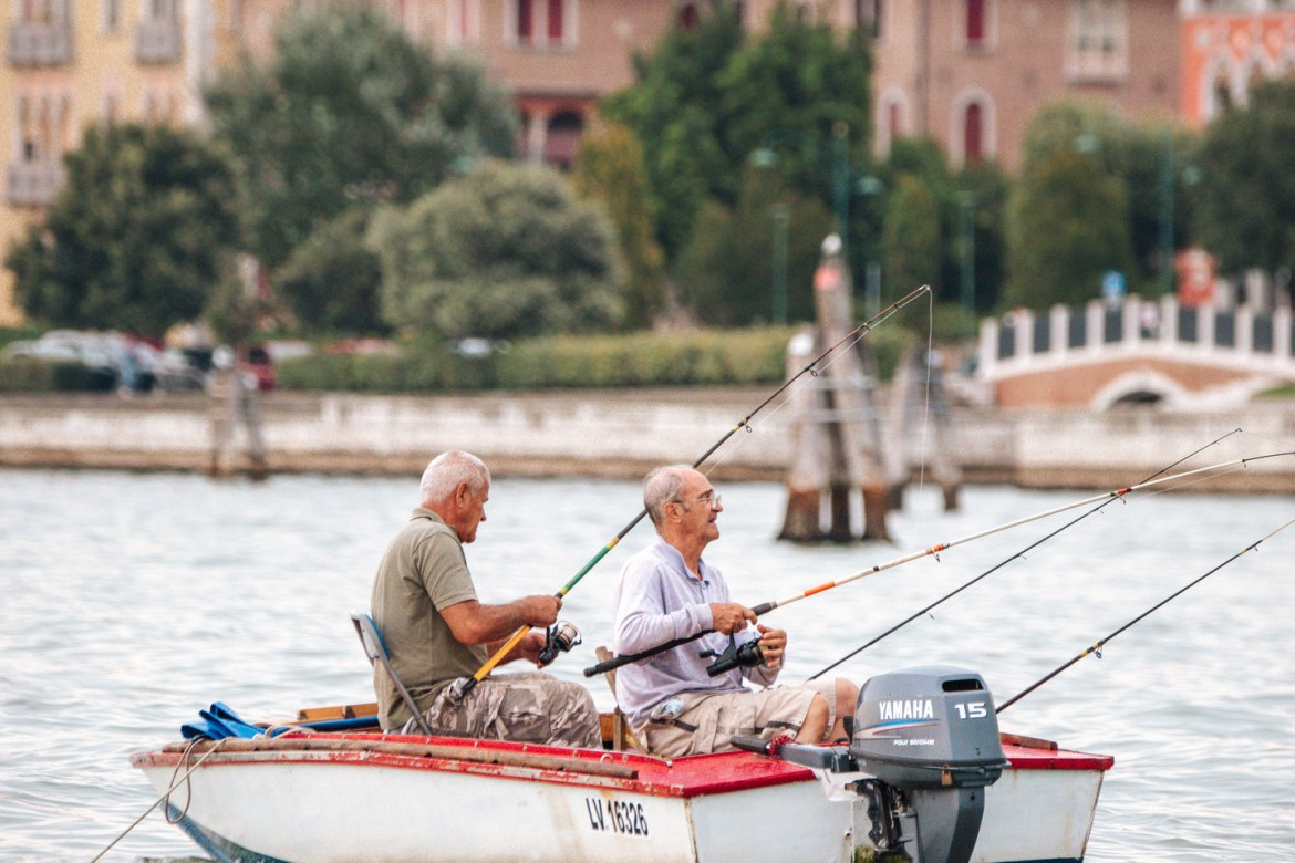 Two older men fish from a small aluminum boat near Venice, Italy.