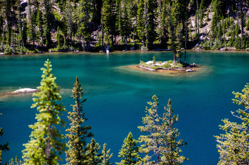 An island in Baron Lake sits surrounded by turquoise, green, and blue waters in the high alpine lake.  The lake sits in the heart of Idaho's Sawtooth National Recreation Area and the Sawtooth Wilderness.