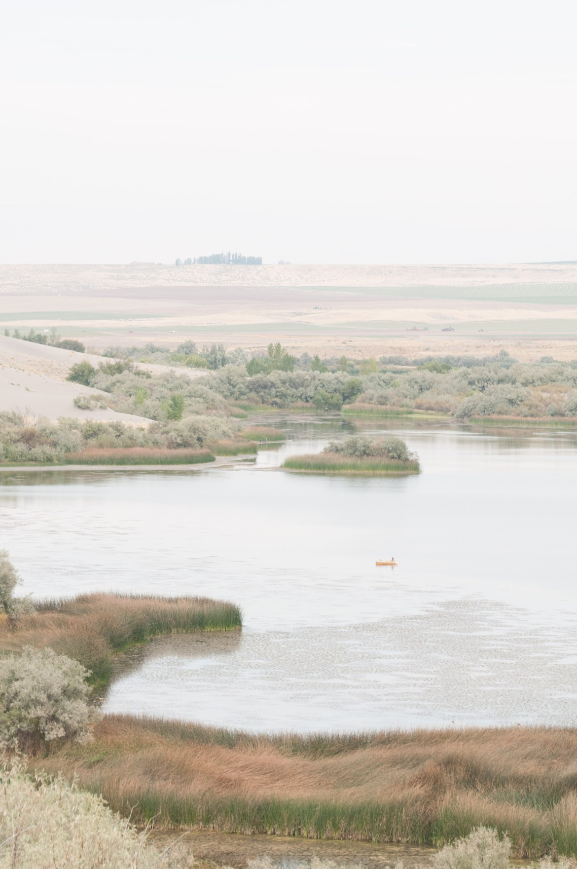 A view to a small lake and the Snake River valley from atop the largest sand dune at Southwest Idaho's Bruneau Sand Dunes State Park. The dunes are the largest free-standing sand dunes in North America.