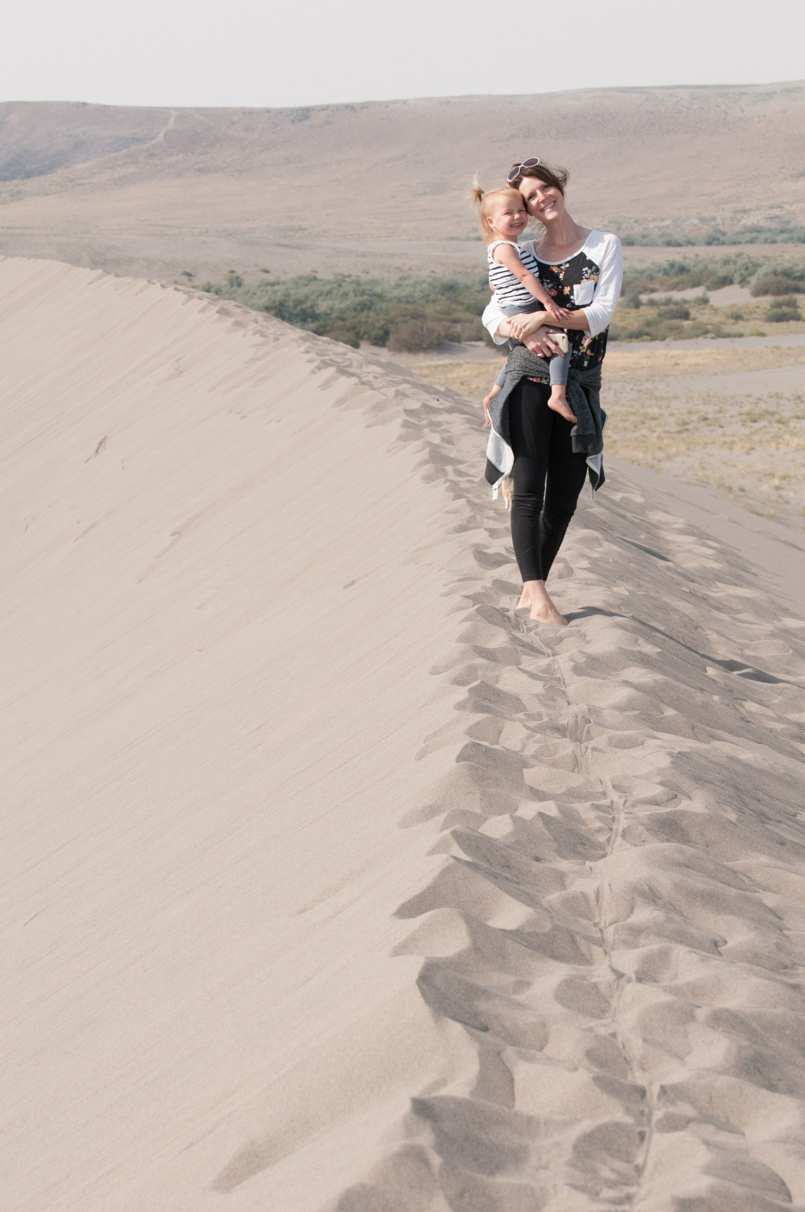 A young girl and her mother stand atop a large sand dune at Southwest Idaho's Bruneau Sand Dunes State Park. The dunes are the largest free-standing sand dunes in North America.