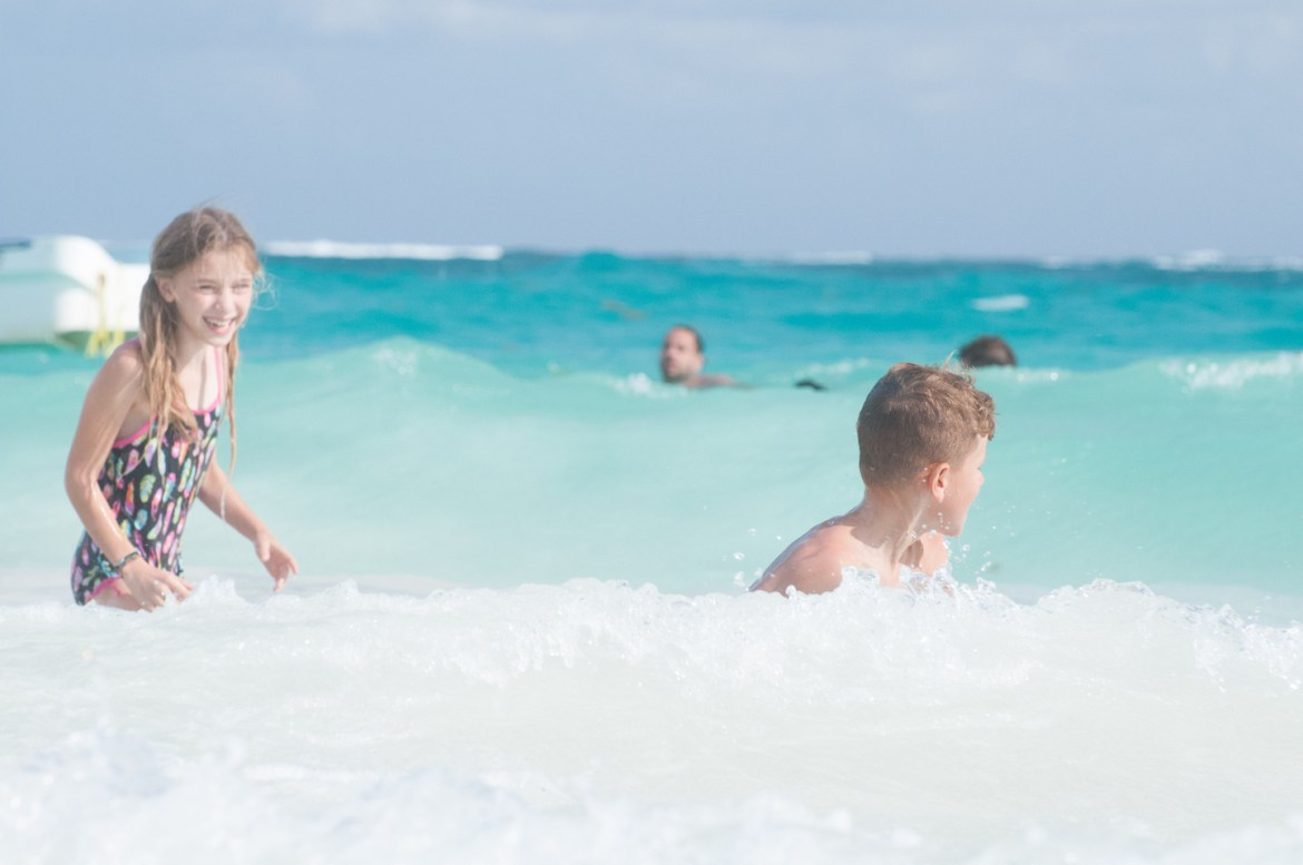 The Best Beach in Tulum: Playa Paraíso. Young children play in the turquoise blue water of the Caribbean Sea at Playa Paraíso, near Tulum, Quintana Roo, Mexico, on the Yucatan Peninsula.  An anchored fishing boat floats further out in the surf, and other swimmers enjoy the warm waters at the best beach in Tulum.