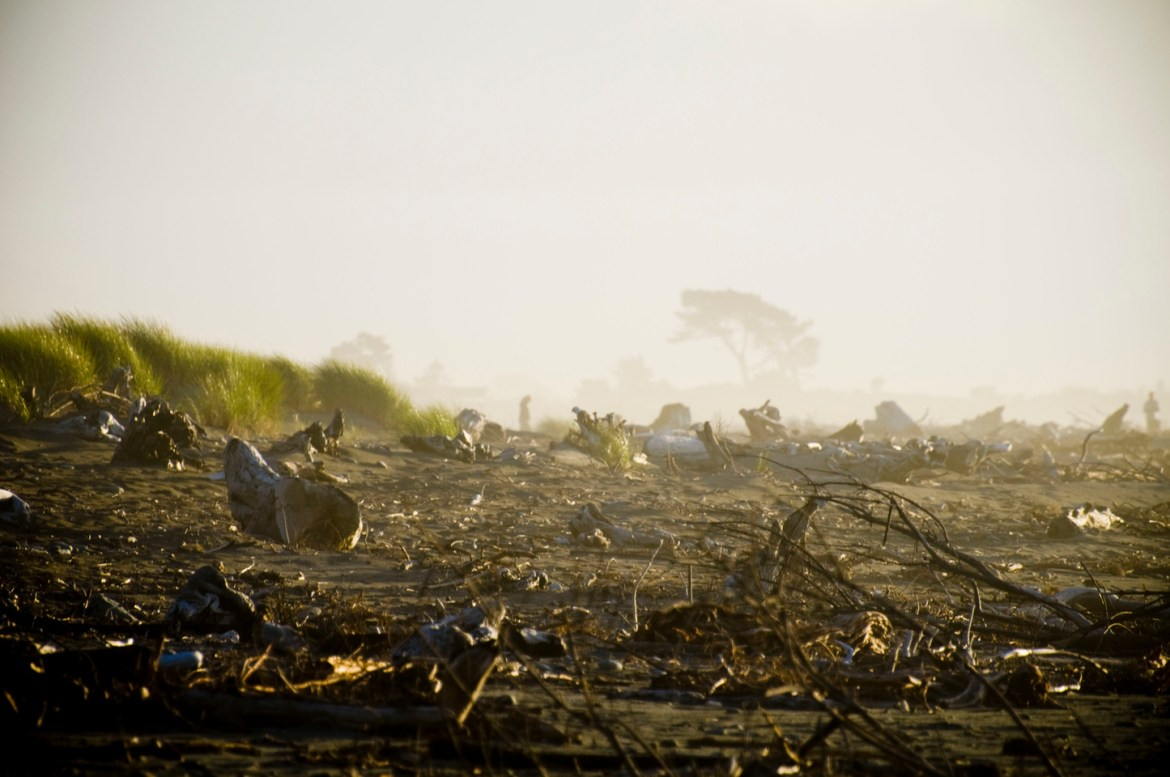 New Zealand South Island Road Trip - Hokitika. A sunset view of Hokitika, New Zealand's West Coast beach, complete with grey sand, driftwood, and other debris.