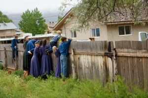 FLDS members watch over a fence as the locks are changed on an empty home in Colorado City, Ariz., Tuesday May 9, 2017, as part of the UEP Trust evictions.