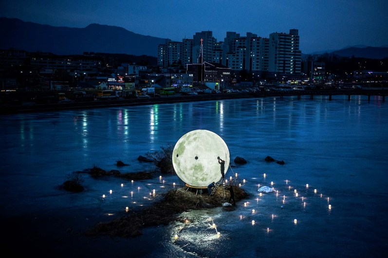 (Chris Detrick | The Salt Lake Tribune) A worker installs an illuminated moon on a frozen river in Gangneung during the Pyeongchang 2018 Winter Olympics on Feb. 19.
