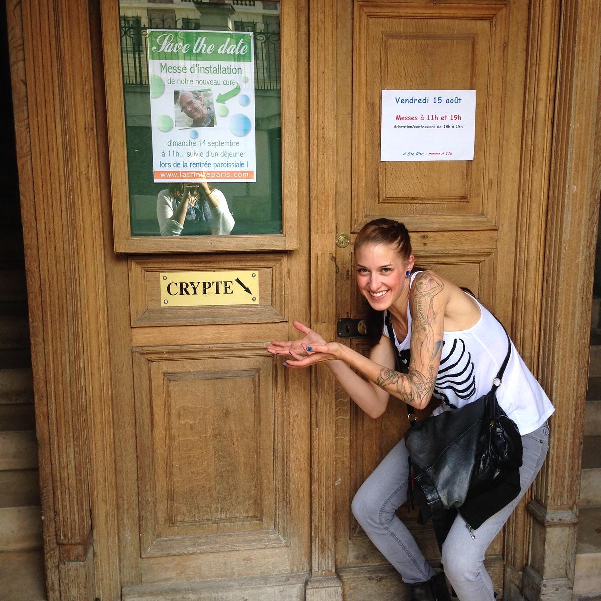 Jennifer Posing Creepily with the Crypt Sign at l'Église de la Sainte-Trinité in Paris, France