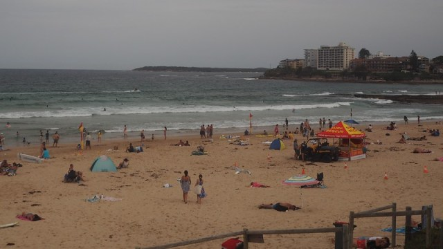 Wide angle view of a busy surf beach.