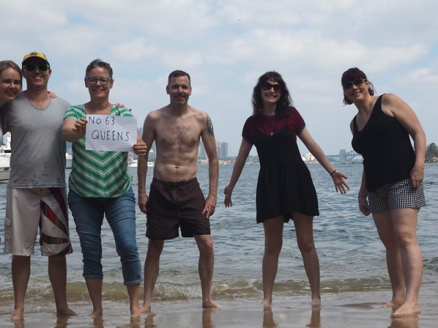 Me and five friends on Queens Beach with a sign which reads: No 63 Queens