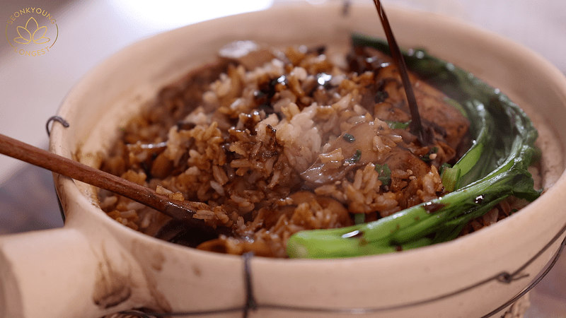 Pouring sauce into Chinese clay pot rice