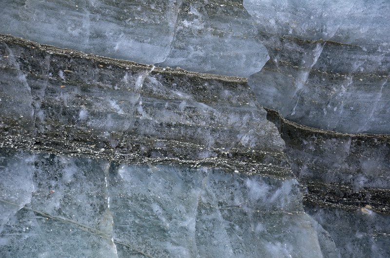 Layers of rock in the glacier ice from inside an ice cave