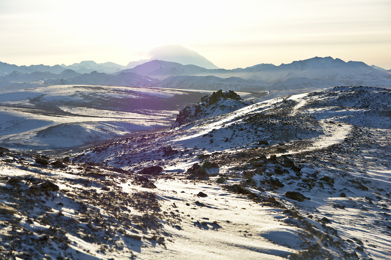 The faint outline of the Savage Alpine Trail from windblown snow looking toward Denali. Winter hiking in Denali National Park.