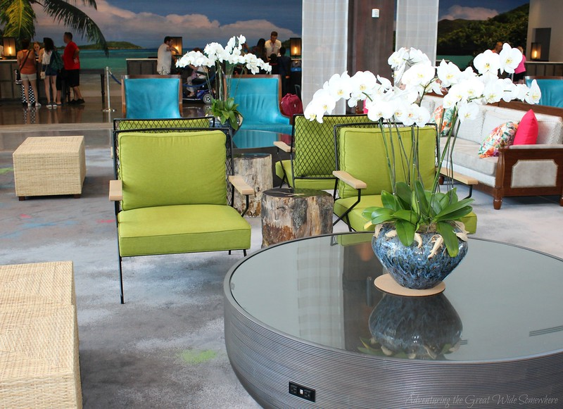 Bright green and aqua lounge furniture and sophisticated white orchids set the tone for a vacation in paradise.