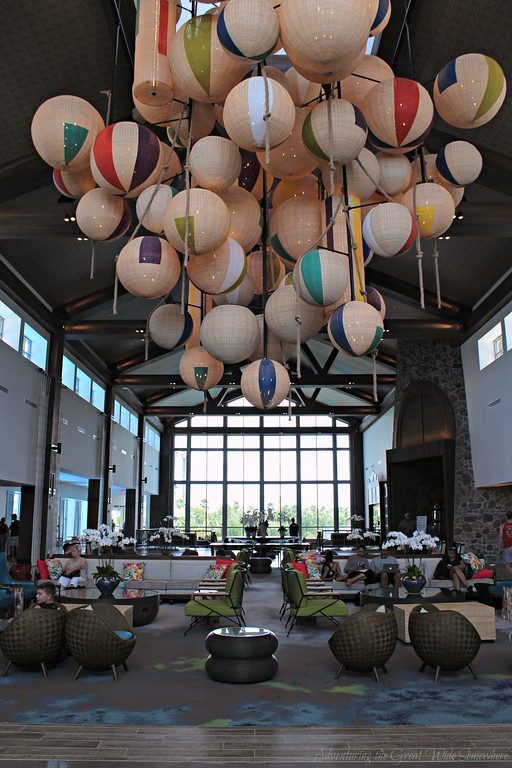 The Sapphire Falls hotel lobby, featuring colorful paper lanterns, modern seating, and a massive wall of windows overlooking the water.