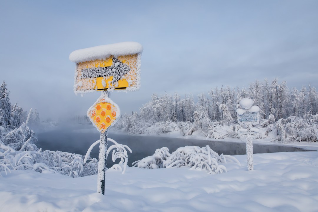 Snow covered turn sign in winter in Fairbanks along the Chena River