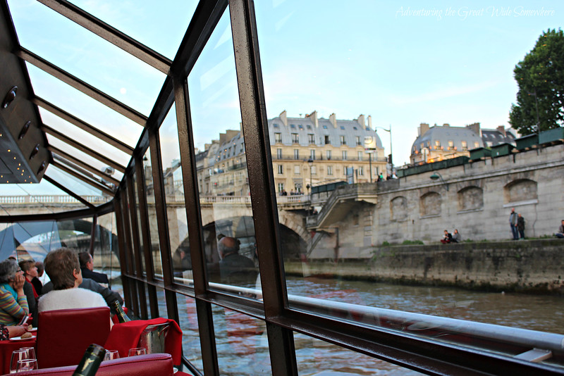 Guests on the Bateaux Mouches dinner cruise look out on the banks of the Seine River