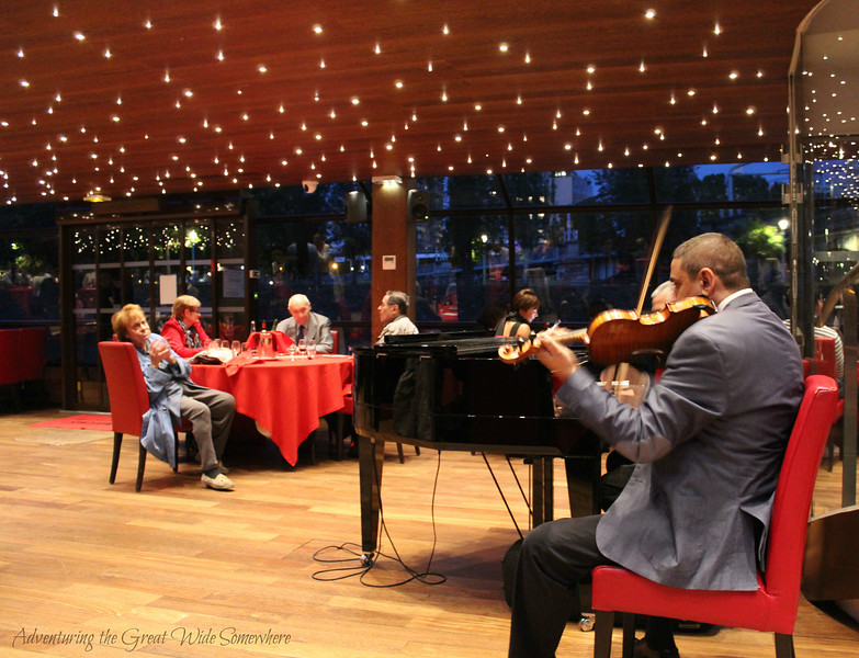 A pianist and violinist play classic French music for guests of the Bateaux Mouches dinner cruise in Paris, France
