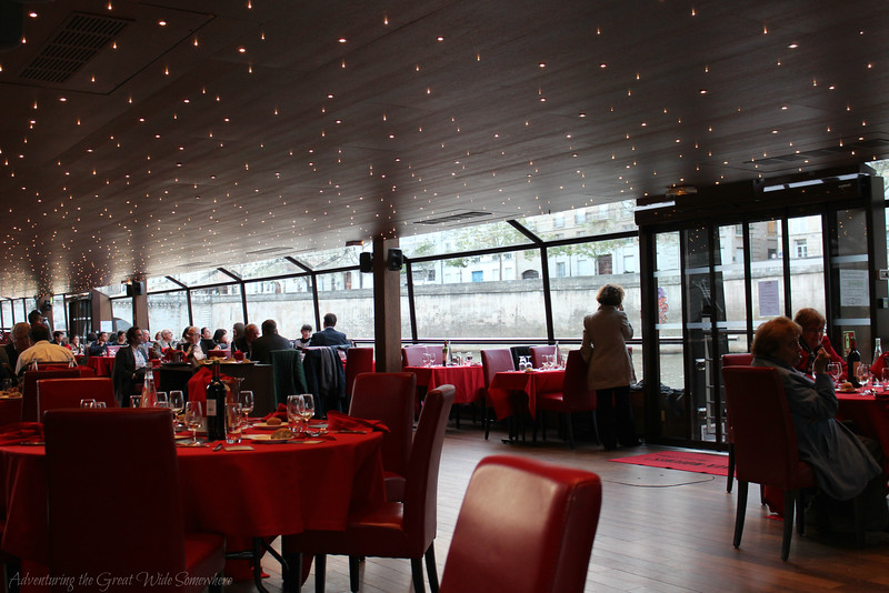The dining area of our Bateaux Mouches dinner cruise, with red table linens, endless windows, and starry lights in the ceiling