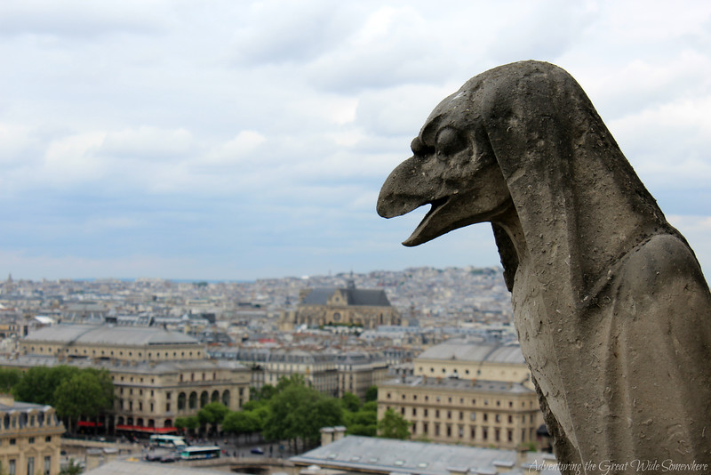 A crow-like gargoyle watches over the beautiful cityscape of Paris, as seen from the towers of Notre Dame Cathedral.