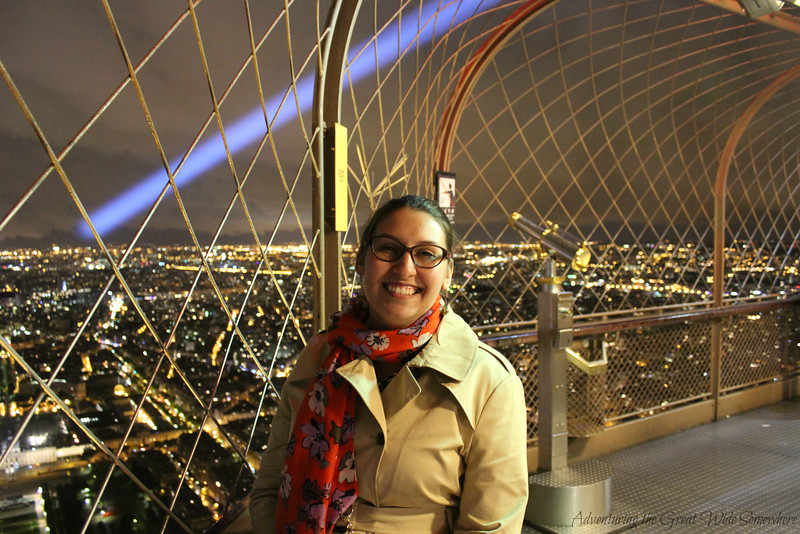 The author standing on the empty top platform of the Eiffel Tower, with the city lit up in the background.