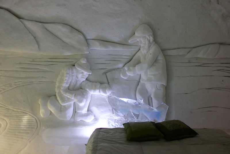 sculpture on wall of men fishing in room of ice hotel