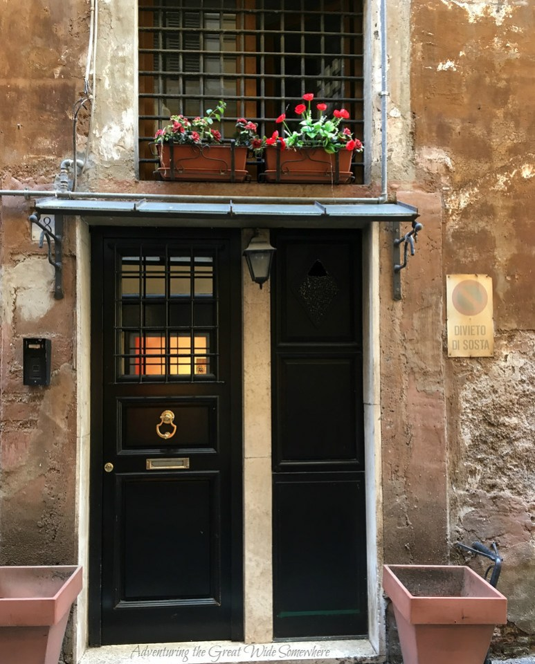 Beautiful Entryway on the Streets of Rome, with Black Door, Gold Knocker, and Colorful Potted Plants