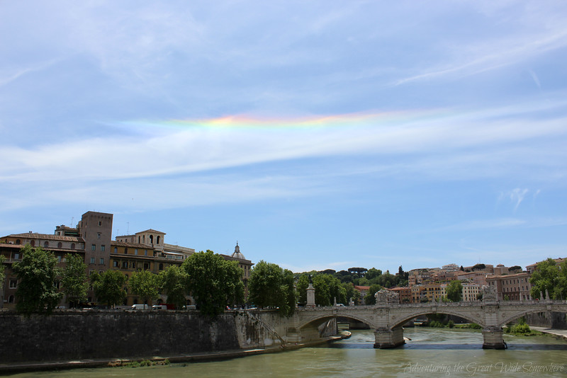 A rainbow streaks through the clouds over the Tiber River in Rome, Italy