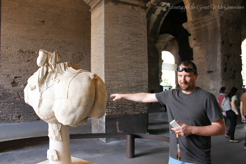 Dan jokingly pointing at the butt of a crumbled statue of a horse at the Colosseum