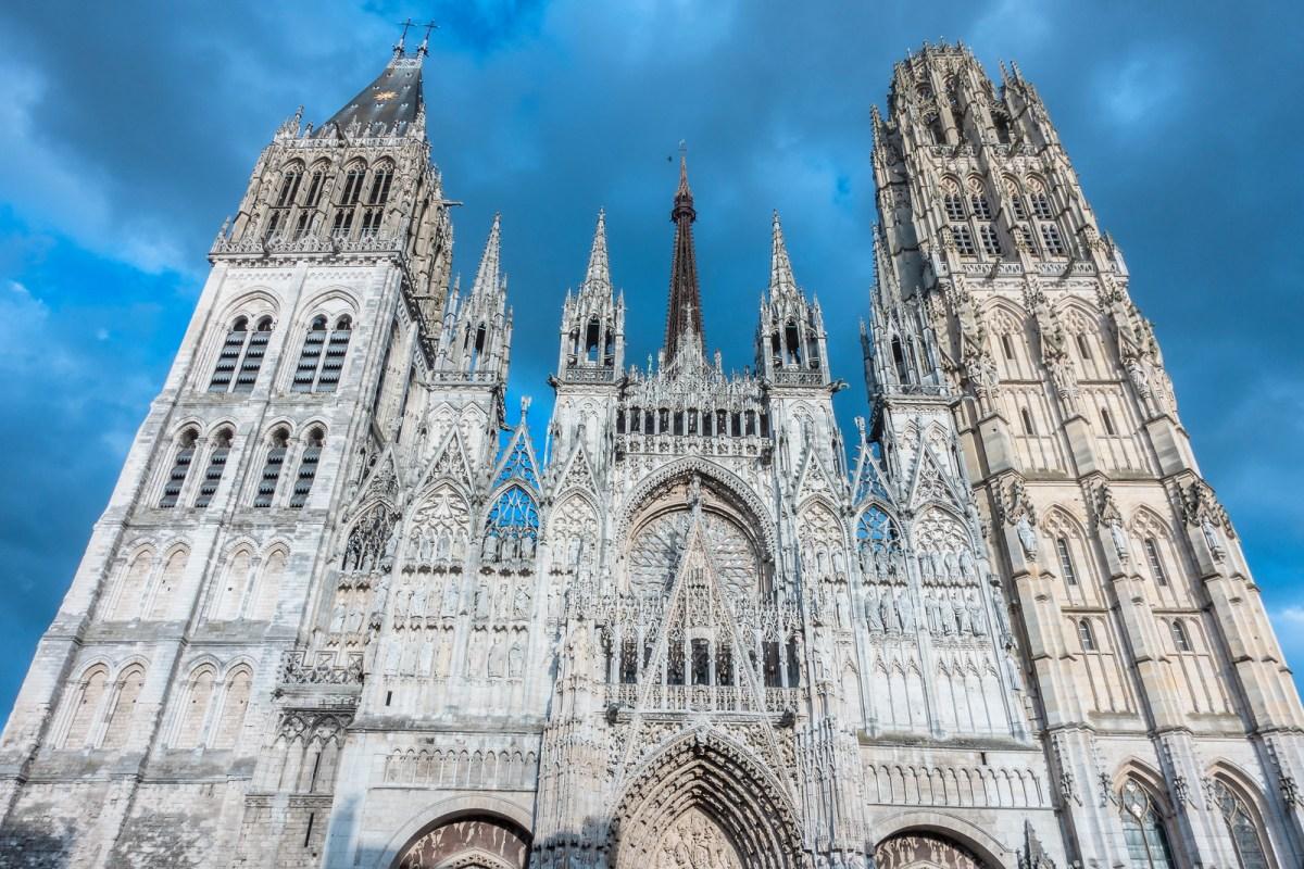 Things to do in Rouen - Notre-Dame de Rouen facade looking beautiful against the grey-blue skye.