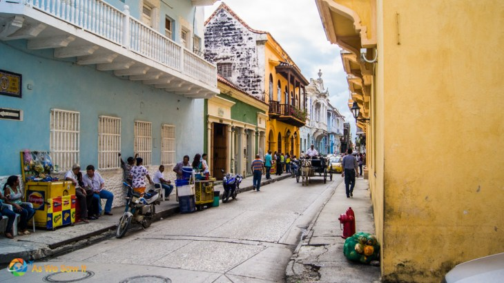 A horse-drawn buggy makes its way down a colorful street in Cartagena.