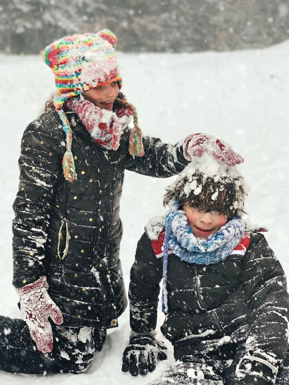 boy and girl play happily in the snow