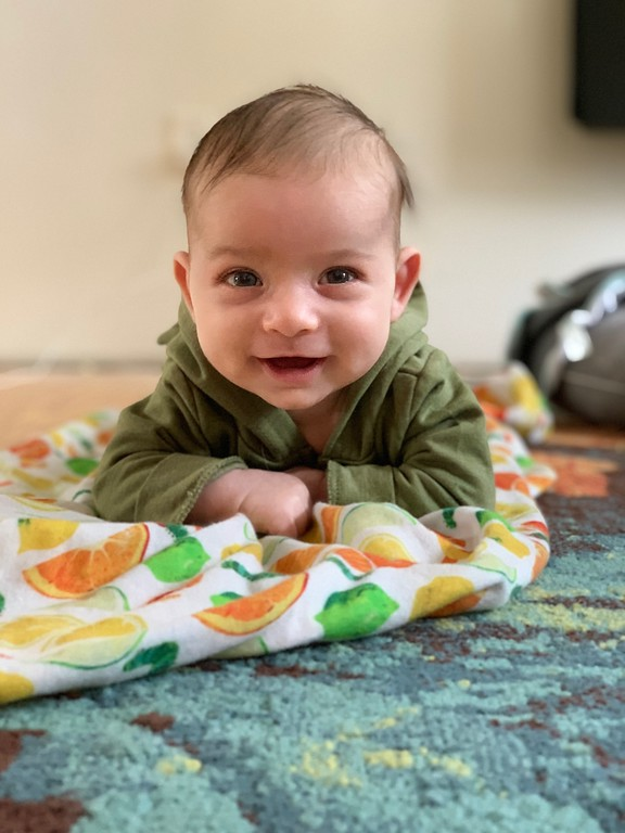 baby boy smiles during tummy time