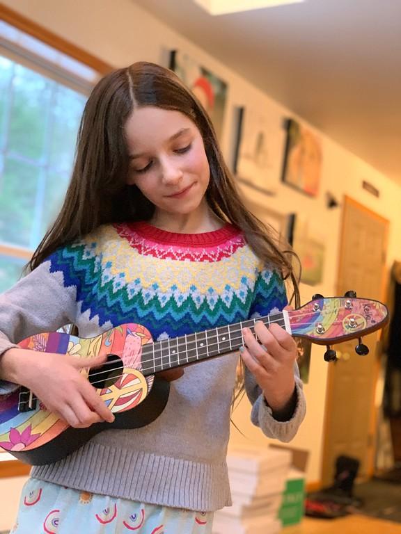 pretty little girl playing ukulele