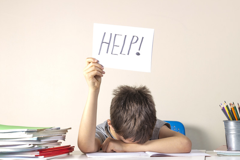 Sad tired frustrated boy sitting at the table with many books and holding paper with word Help. Learning difficulties, education concept.